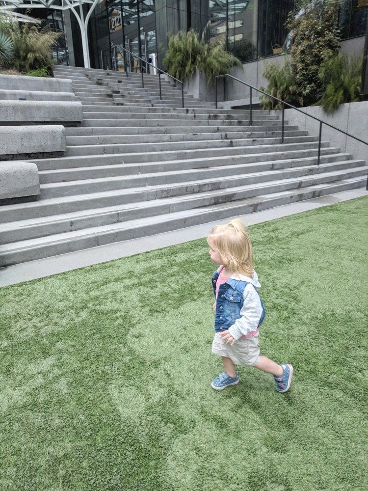 Melody running in park next to Amazon Spheres