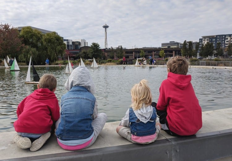 Kids watching toy sailboats