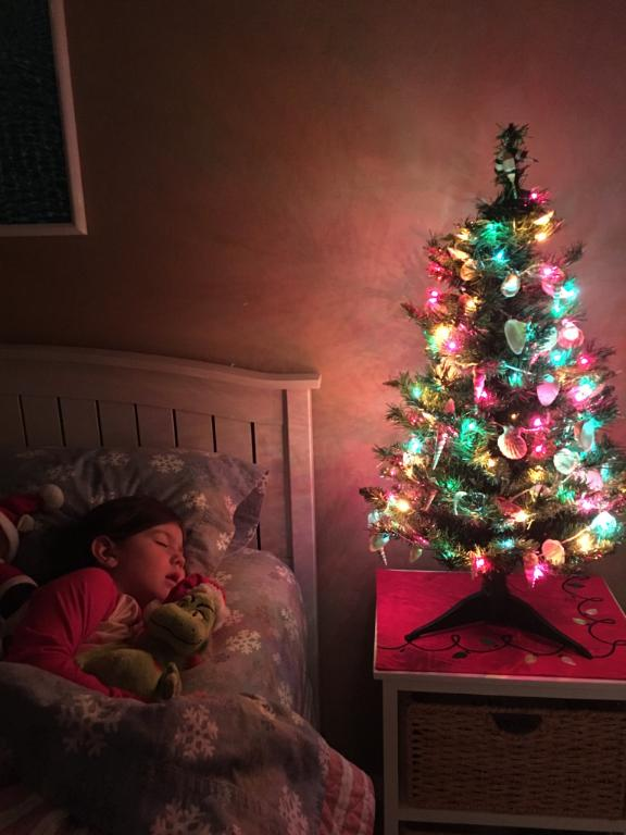 child sleeping by a christmas tree