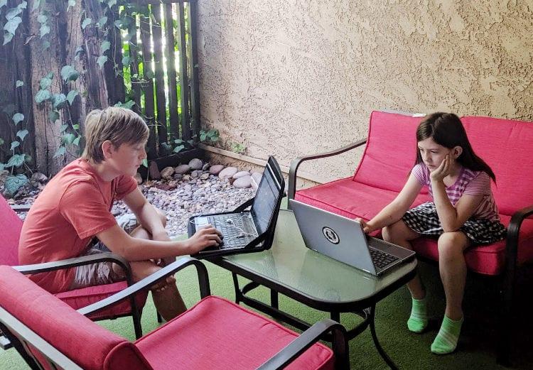 kids on laptops on patio